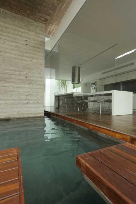 Perpaduan warna putih dan elemen kayu untuk desain kolam renang indoor (Sumber: design-milk.com)