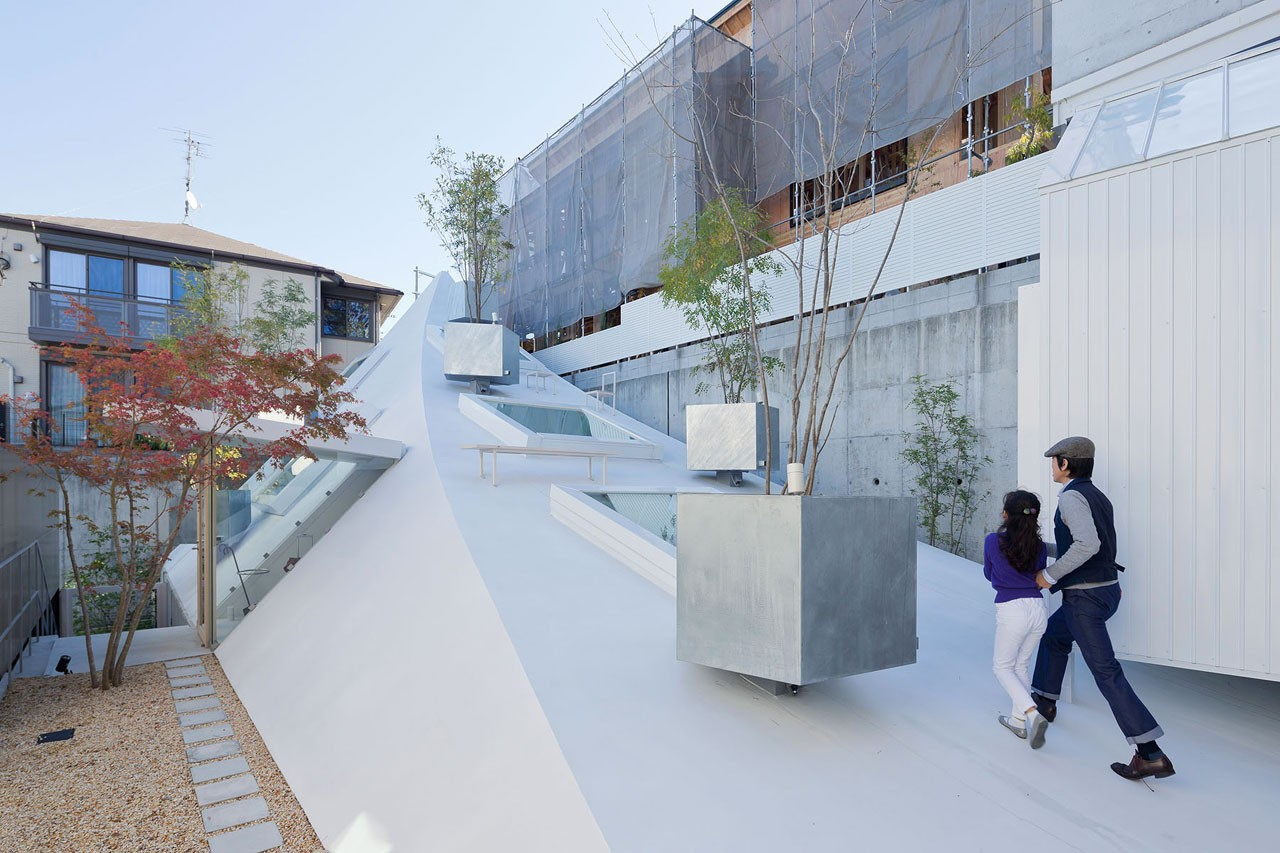 House K karya arsitek Jepang Sou Fujimoto adalah hasil pendekatan yang cerdas terhadap sebuah lahan yang dikelilingi oleh pemukiman perkotaan yang padat di tiga sisi dan juga dibatasi oleh rumpun pepohonan. Rumah ini berbentuk bulan sabit, yang berfungsi sebagai hunian keluarga, yang tampak menonjol di atas permukaan tanah seperti batu karang sekaligus mengubah keseluruhan permukaan atap menjadi area teras yang nyaman.