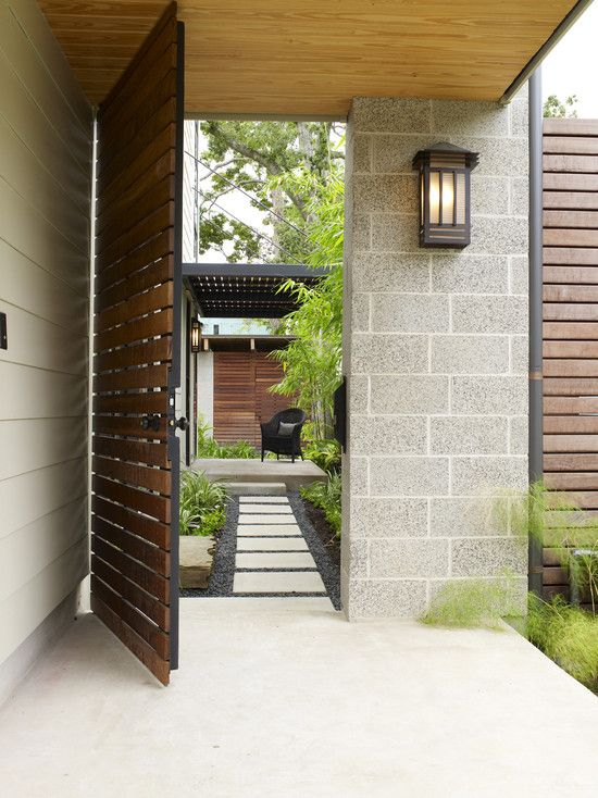 Pintu menuju teras samping? Mungkin Anda menyukai tipe ini. Pintu dengan rangka besi dan daun pintu dari panel kayu memberi kesan semi-transparan. Terhubung ke jalan setapak, area taman di pinggir jalan setapak, dan area tempat duduk, pintu ini menciptakan serial vista. Pintu ini secara vertikal mencapai langit-langit. Tipe ini jelas lebih besar daripada yang diperlukan secara fungsional, dan dengan demikian memiliki berbagai aturan yang berbeda.