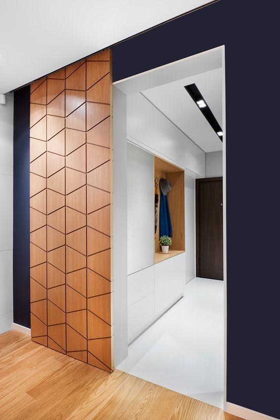 Berikut ini adalah contoh lain dari pintu geser yang berfungsi sebagai dinding. Rel geser pada pintu ini tersembunyi di langit-langit yang memberikan proporsi ruang dan aksen dinding warna gelap yang menonjolkan ukuran panel. Jadi, panel kayu berpola dan dinding dengan warna cat biru tua menjadi elemen menonjol lainnya dalam pilihan material arsitektur selain lantai parquette. Namun, untuk panel pintu geser seperti ini, Anda bisa mengunakan hampir semua bahan, seperti kaca, cermin, metal berpola, dan sebagainya. Selain berfungsi baik sebagai penghubung ke ruang privasi kamar tidur, pintu geser ini juga dapat menjadi objek seni.