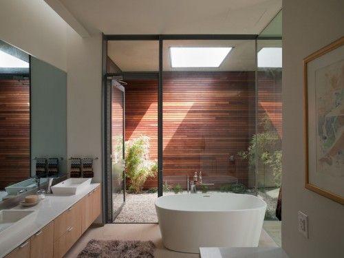 Sistem pintu komersial dan industri adalah perangkat yang sangat baik untuk mengubah persepsi skala. Di dinding kamar mandi ini, pembagian tiang jendela membuat ruang ini tampak lebih tinggi daripada sesungguhnya. Memasukkan sistem jendela dan pintu eksterior di dalam ruangan telah menciptakan area publik pada ruang yang sangat pribadi.